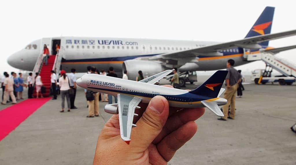 Een hand houdt een miniatuurvliegtuig vast met op de achtergrond het echte toestel.