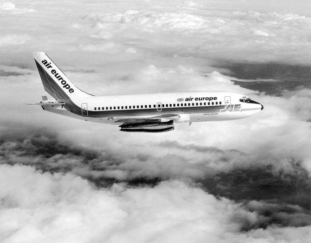 Een vliegtuig van het model Boeing 737 vliegt boven de wolk op een zwart-wit beeld.