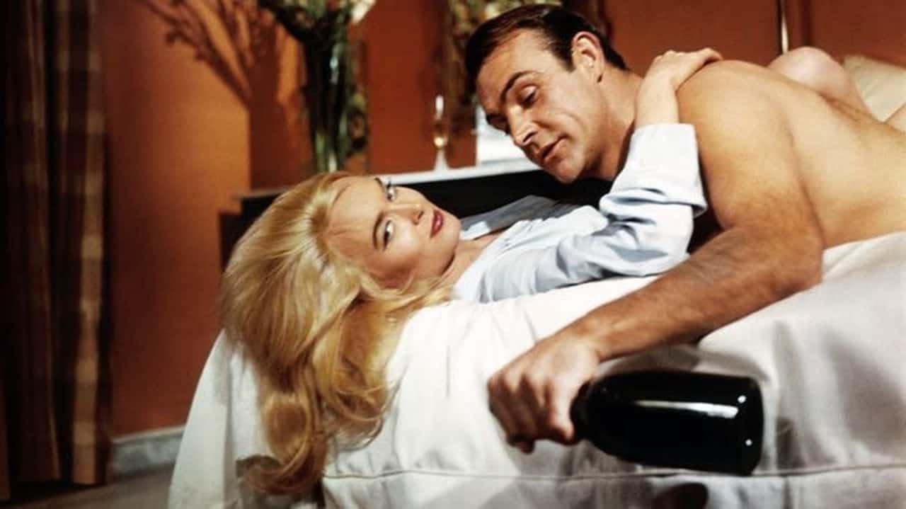 James Bond est au lit avec une femme et tient une bouteille
