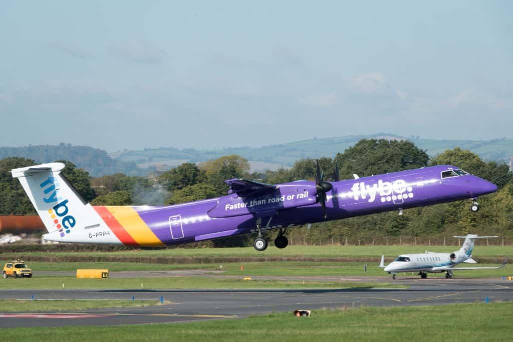 Een blauw vliegtuig van low cost-maatschappij Flybe stijgt op.