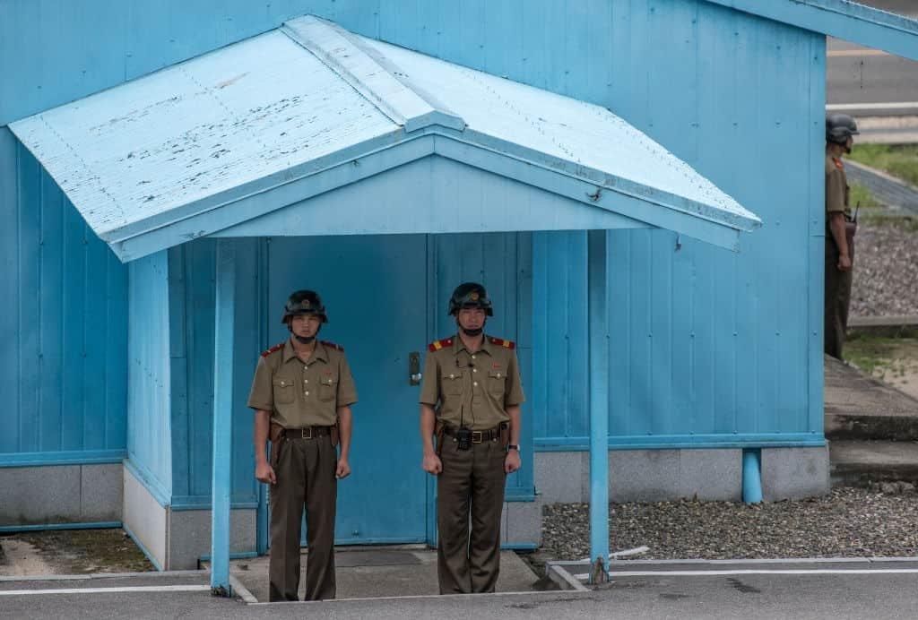 Twee soldaten van Noord-Korea staan met de armen strak naast lichaam voor een blauw gebouw met afdak.