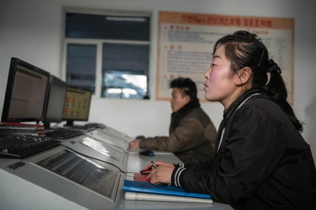 Een vrouw kijkt in Noord-Korea naar het scherm van een computer, op de achtergrond doet een man hetzelfde.