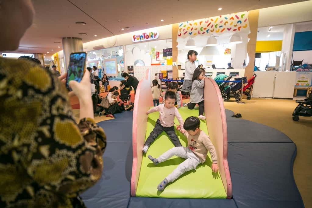 Zuid-Koreaanse kinderen glijden van een kleine gele glijbaan in het midden van een winkelcentrum.