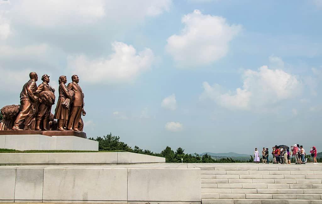Een groep toeristen kijkt in Pyongyang naar enkele standbeelden van het regime van Noord-Korea.