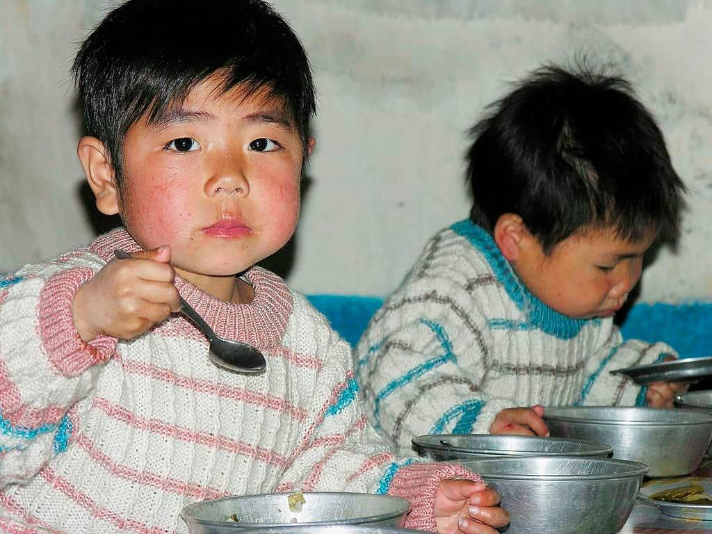 Een kind met een lopende neus houdt een lepel vast terwijl hij naast een ander kind in Noord-Korea eet.