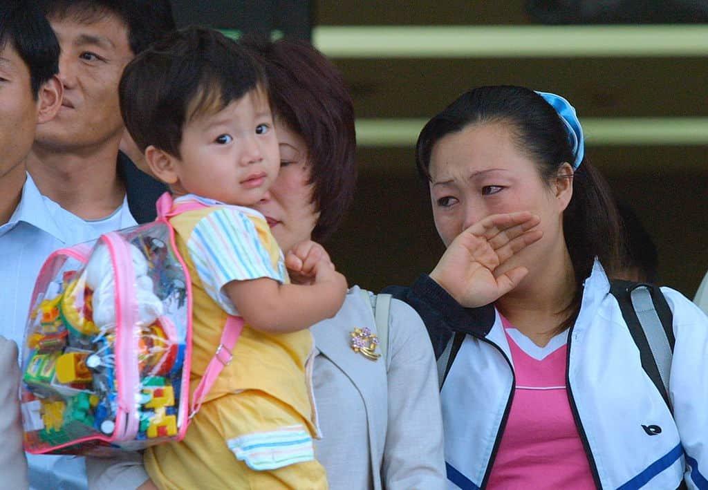 Twee vrouwen en een kind kijken emotioneel toe wanneer ze als vluchtelingen in Zuid-Korea aankomen.