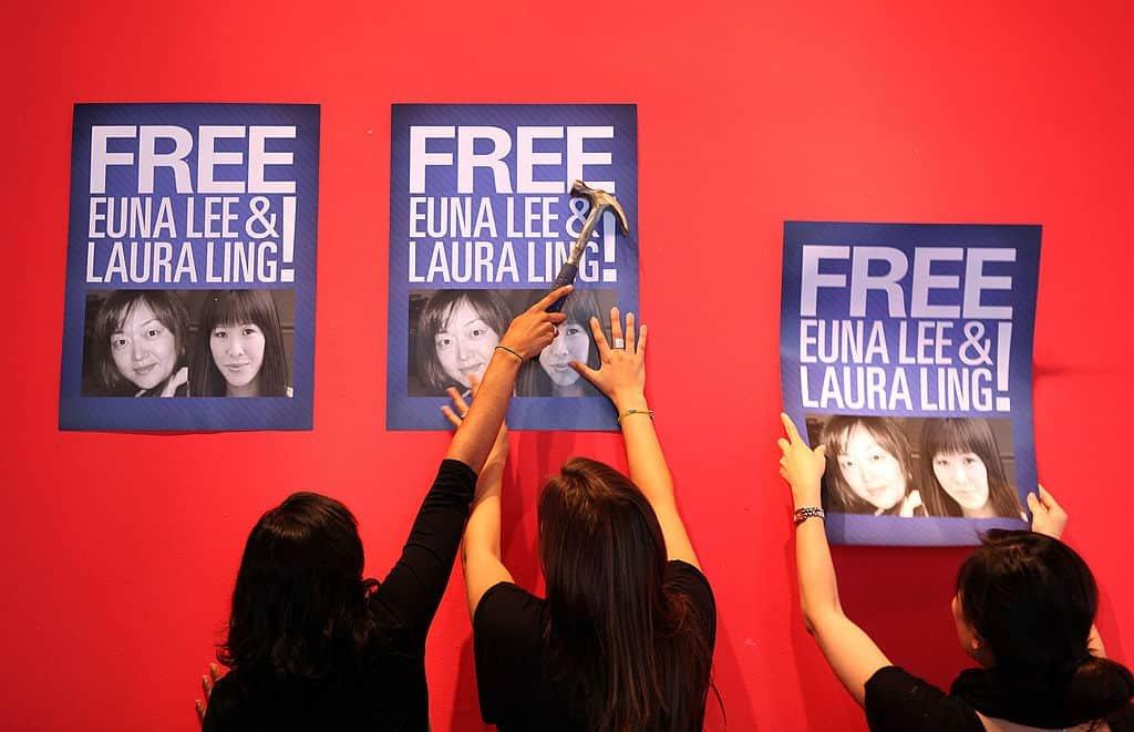 Drie vrouwen hangen affiche met de eis tot vrijlating van een vrouw uit een gevangenis in Noord-Korea op een rode muur.