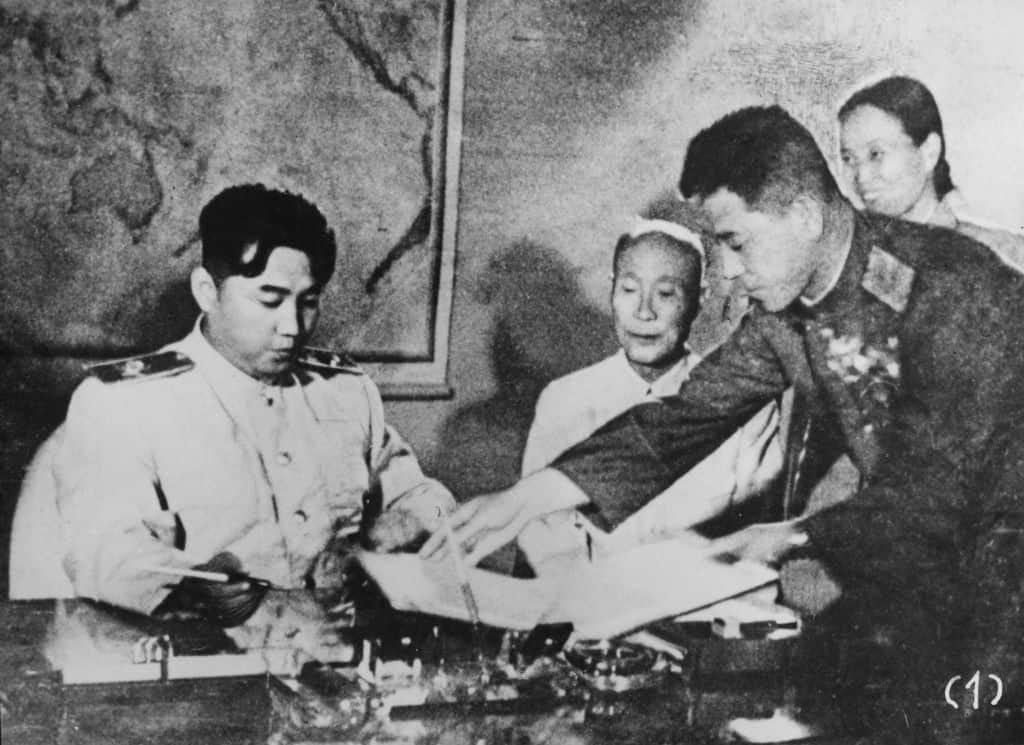 Een zwart-wit beeld van Kim Il-sung die een document te lezen krijgt.