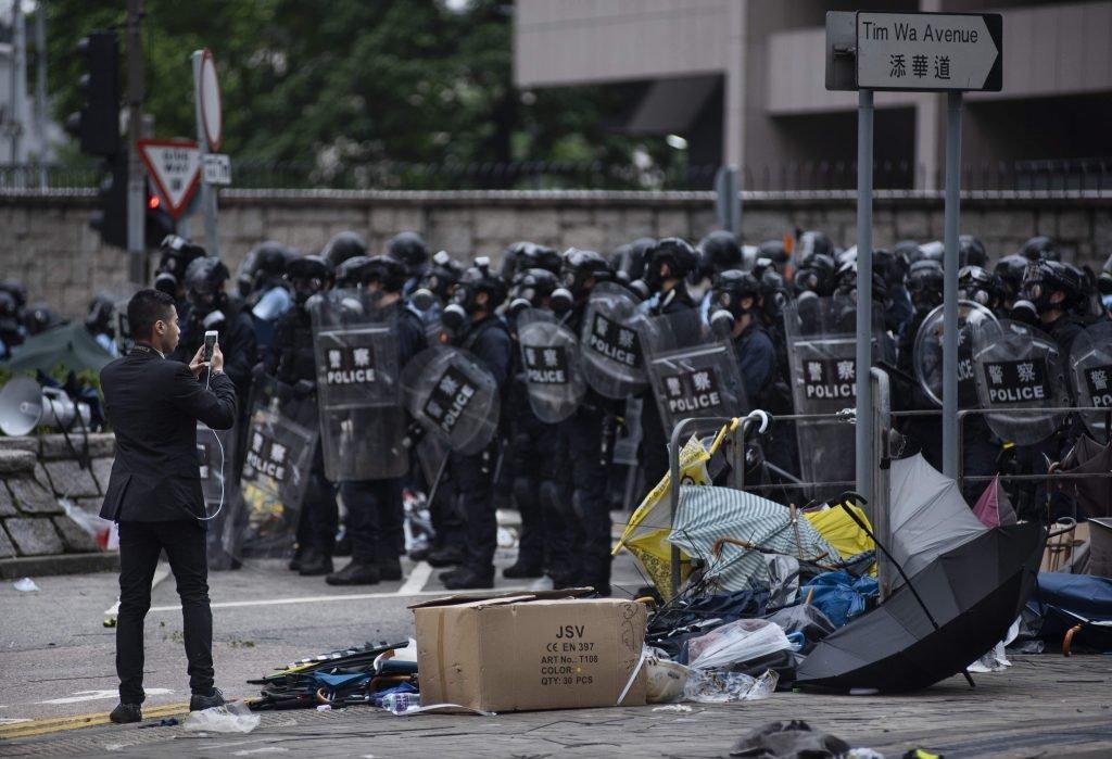 Een man trotseert de Hongkongse veiligheidstroepen met zijn smartphone-camera, tijdens de begindagen van de protesten tegen de toenemende Chinese invloed in de semi-autonome regio, intussen meer dan een jaar geleden. - Isopix