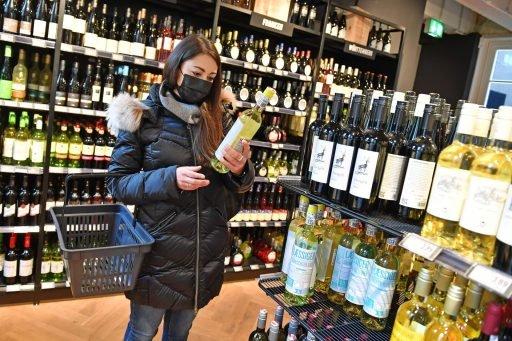 Vrouw koopt wijn in de supermarkt