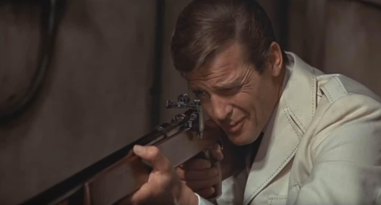 Roger Moore comme James Bond regarde à travers la vue d