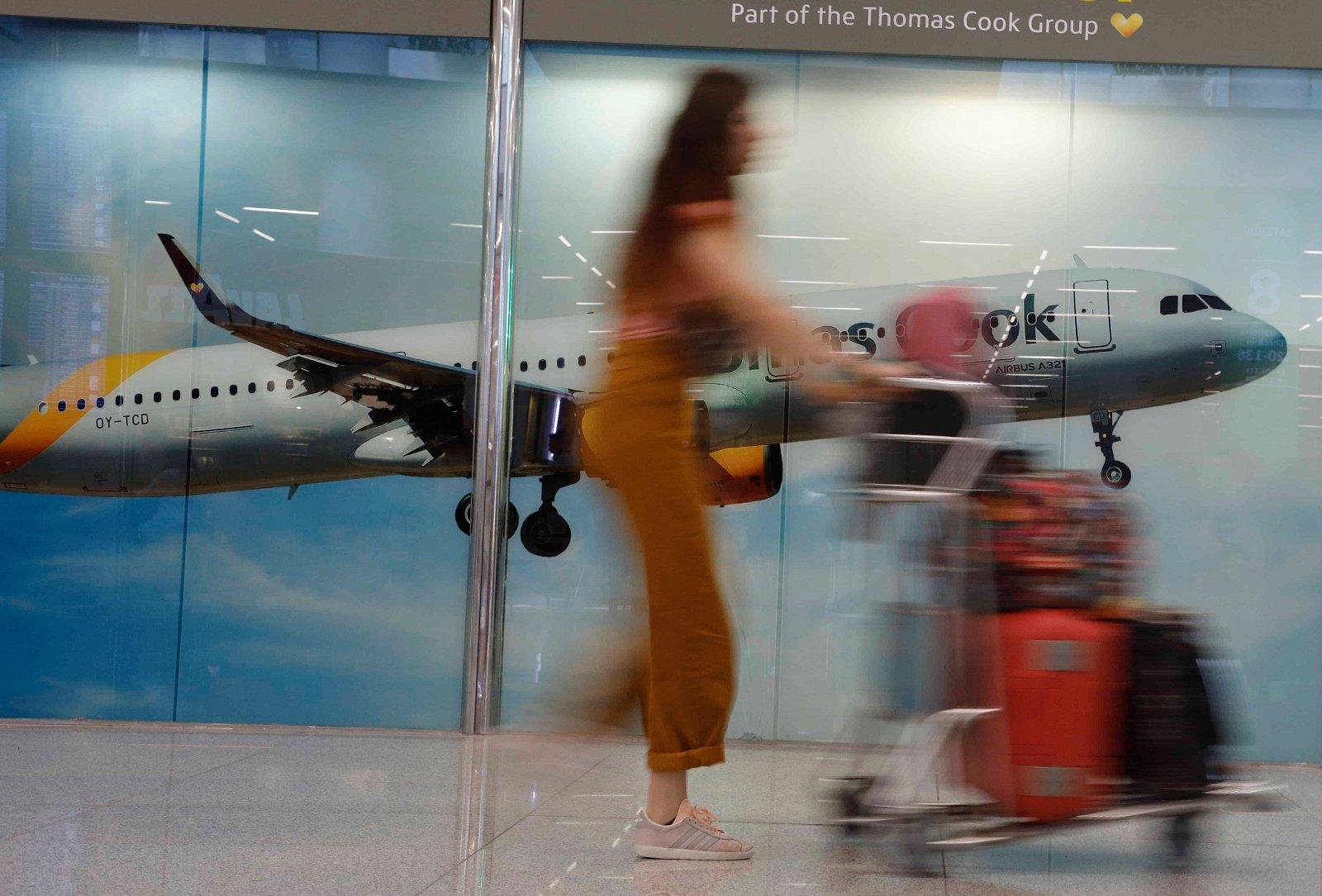 Een man in werkkledij staat aan de deur bij de staart van een vliegtuig van Thomas Cook.