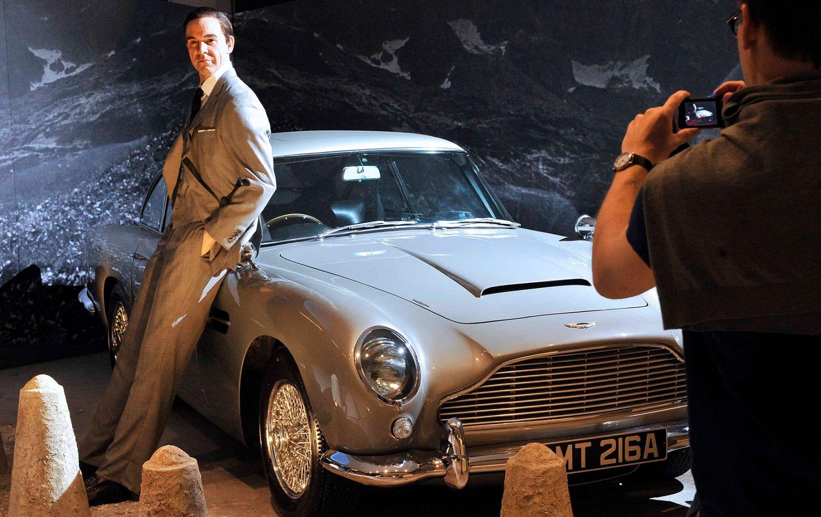 Un visiteur dans un musée prend en photo une statue de cire de Sean Connery appuyé contre une voiture.