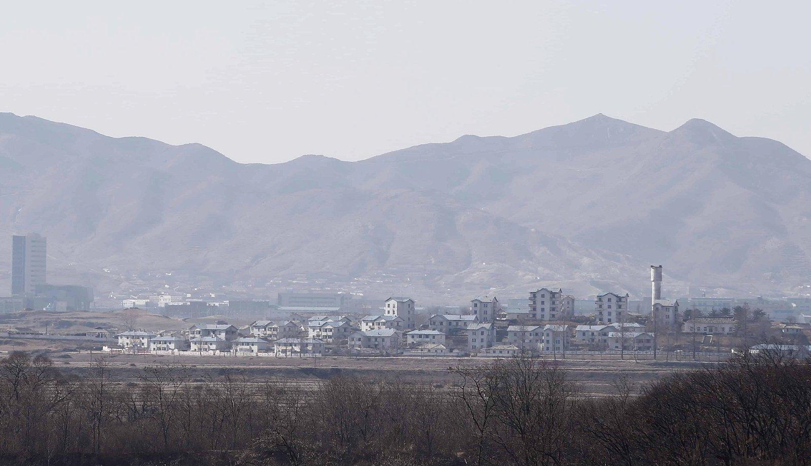 Een beeld op afstand van de stad Kijong-dong in Noord-Korea, met bergen op de achtergrond.