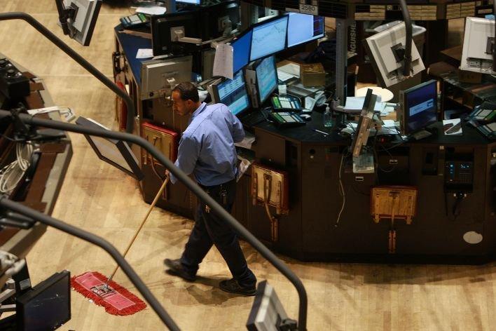 Un homme passe le balai dans la salle de marchés d