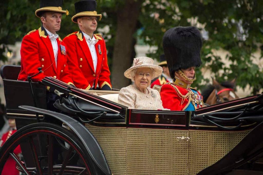 Koningin Elizabeth II in een open rijtuig met Prins Philip